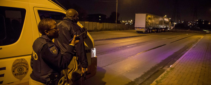 JMPD officers take cover behind a vehicle after receiving live fire near Jeppestown in Johannesburg's CBD. Picture: Thomas Holder/EWN.
