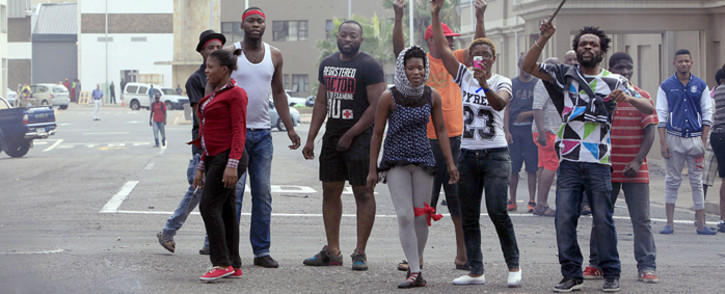 FILE: Foreign nationals gesture after clashes broke out between a group of locals and police in Durban on 14 April, 2015 in ongoing violence against foreign nationals in Durban, South Africa. Picture: AFP.
