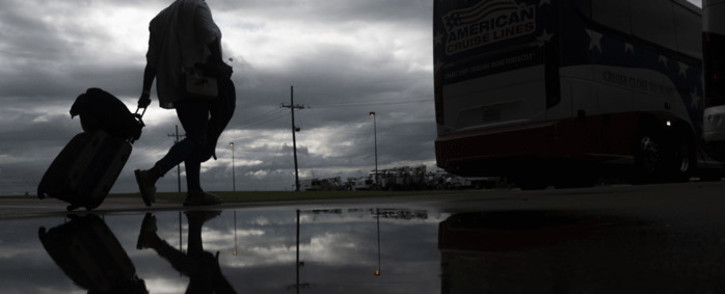 A woman rolls a suitcase as she walks to board a bus for evacuation before the arrival of hurricane Laura in Lake Charles, Louisiana on 25 August 2020 amid the coronavirus pandemic. Picture: AFP