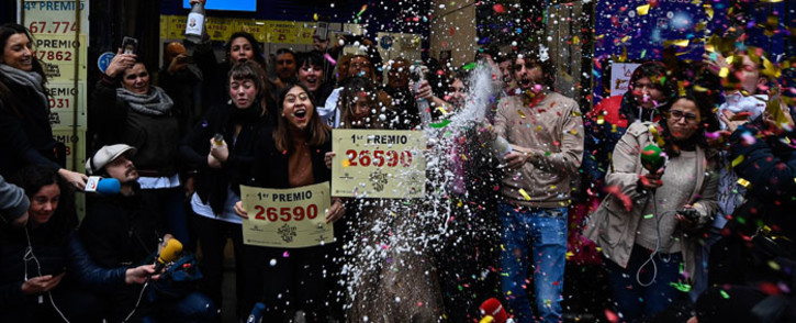 """Doña Manolita Lottery Administration shop employees celebrate having sold the winning number 26590, that represents takings of €4 million (£2.9 million) of Spain's Christmas lottery named """"El Gordo"""" (Fat One) in Madrid on 22 December 2019. Picture: AFP"""