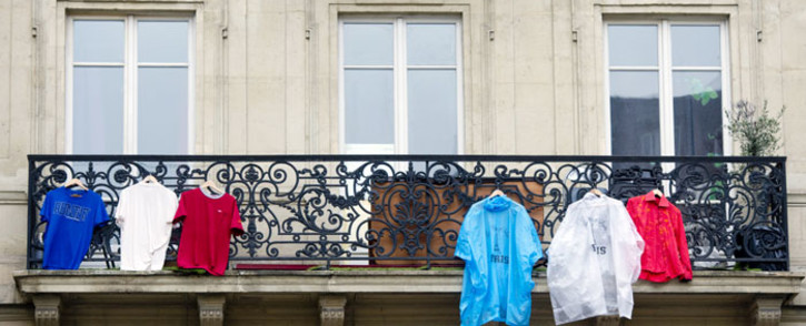 T-shirts and coats hang on a balcony in Paris, in arrangements to re-create the tri-colours of the French national flag in memory of the 130 victims of the November 13, 2015 coordinated terror attacks in Paris claimed by the Islamic State group (IS). Picture: AFP