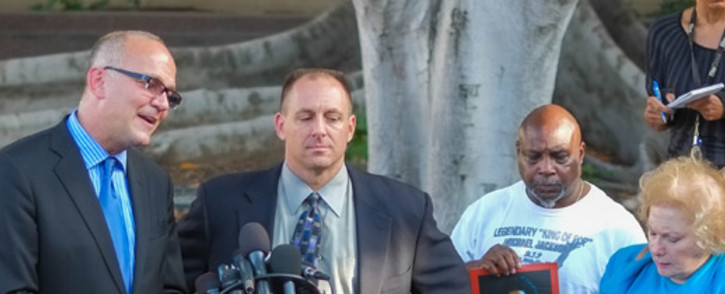 AEG Attorney Marvin Putnam (L) with Shawn Threll (C) speaks to the media after the AEG Jackson trial verdict on 2 October, 2013. Picture: AFP