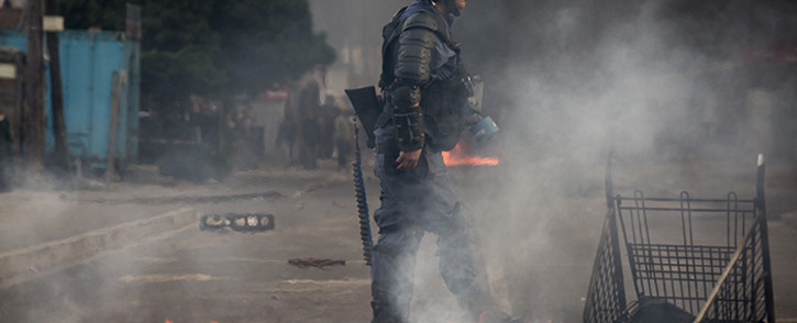 FILE: A Public Order Police officer walks passed a pile of burning debris used as a roadblock during riots. Picture: Thomas Holder/EWN