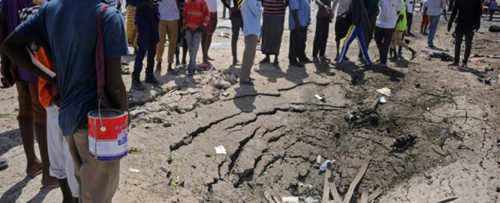 People stand next to damages at the scene of a car bombing attack in Mogadishu, Somalia, on 22 December 2018. Picture: AFP.