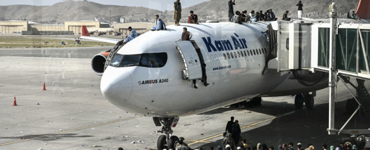 Afghan people climb atop a plane as they wait at the Kabul airport in Kabul on 16 August 2021, after a stunningly swift end to Afghanistan's 20-year war, as thousands of people mobbed the city's airport trying to flee the group's feared hardline brand of Islamist rule. Picture: Wakil Kohsar/AFP