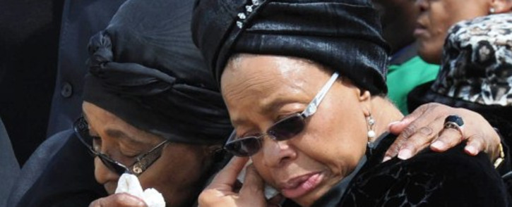 FILE: Nelson Mandela's wife Graça Machel (R) and ex-wife Winnie Madikizela-Mandela leaving Mthatha Airport after the arrival of his body, 14 December 2013. Picture: GCIS.