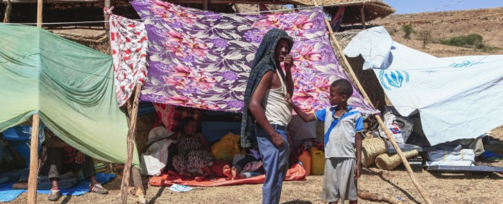 FILE: Ethiopian refugees who fled fighting in Tigray province stand outside a hut at the Um Rakuba camp in Sudan's eastern Gedaref province, on 16 November 2020. Picture: AFP.