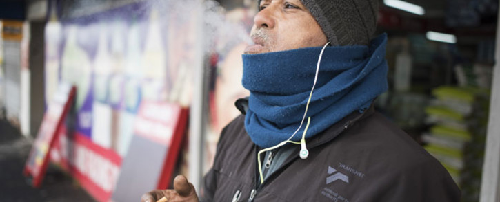 A man enjoys one of his favourite brands of cigarettes outside a shop in Athlone, Cape Town, as cigarettes are unbanned after South Africa moved to level 2 of the coronavirus lockdown on 18 August 2020 in Cape Town. Picture: AFP