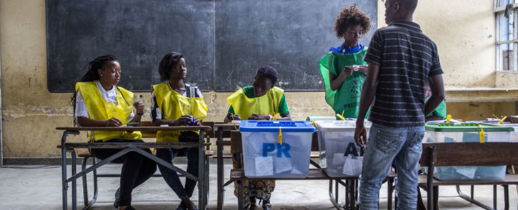 National Electoral Commission (CNE) officials check a voter's ID at Munhava Central Primary School in Beira, Mozambique on 15 October 2019. Picture: AFP