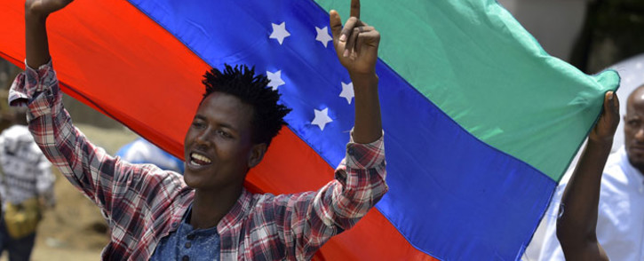 In this file photo taken on 15 July 2019 A young man reacts in front of the unofficial green, blue and red flag of the advocated region for the Sidama ethnic group as people of the Sidama ethnic group, the largest in southern Ethiopia. Picture: AFP