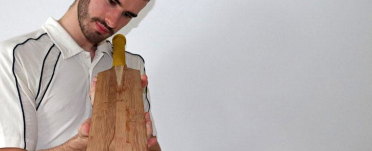 An undated handout image released by The University of Cambridge and received in London on 10 May 2021 shows Ben Tinkler-Davies, the co-author of a paper looking into replacing Willow with Bamboo as a material for making cricket bats, studying a bamboo bat. Picture: University of Cambridge/AFP