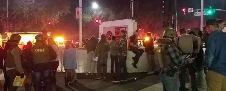 This photo obtained on 8 November 2018 courtesy of Jeremy Childs twitter account shows police officers interviewing people outside a country music bar and dance hall in Thousand Oaks, in the Los Angeles-area, after a gunman barged into a large, crowded venue and opened fire late 7 November. Picture: AFP.