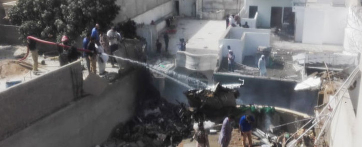 FILE: Rescue workers spray water on the part of a Pakistan International Airlines aircraft after it crashed at a residential area in Karachi on 22 May 2020. Picture: AFP