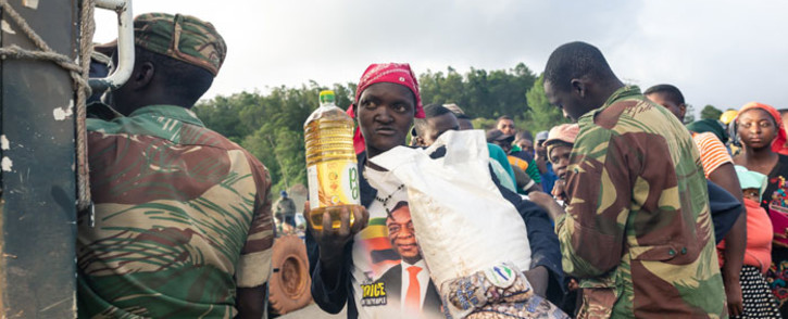 FILE: A picture taken on 18 March 2019 shows villagers receiving food handouts during search and rescue operations in the wake of devastating floods and mudslides caused when Cyclone Idai struck Zimbabwe in Chimanimani. Picture: AFP