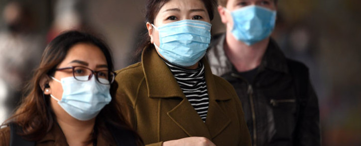 Commuters walk outside Melbourne's Flinders Street Station on 23 July 2020 on the first day of the mandatory wearing of face masks in public areas as the city experiences an outbreak of the COVID-19 coronavirus. Picture: AFP