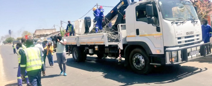 JMPD officers and City Power officials conducted an illegal electricity connection operation in Alexandra on 21 September 2021. All exit streets were then closed off by protesting residents with burning tyres and big stones. Picture: JMPD.