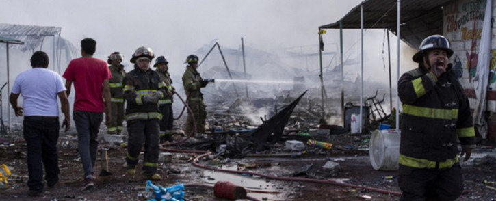 Firefighters work amid the smouldering ruins left by a blast in a fireworks market killing at least 26 and injuring dozens, in Mexico City, on December 20, 2016.