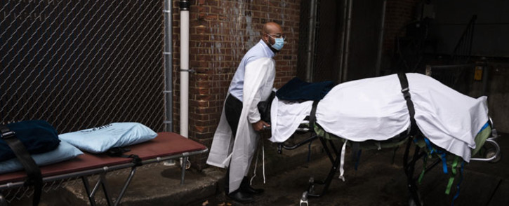Maryland Cremation Services transporter Reggie Elliott brings the remains of a COVID-19 victim to his van from the hospital's morgue in Baltimore, Maryland, in the United States on 24 December 2020. Picture: AFP
