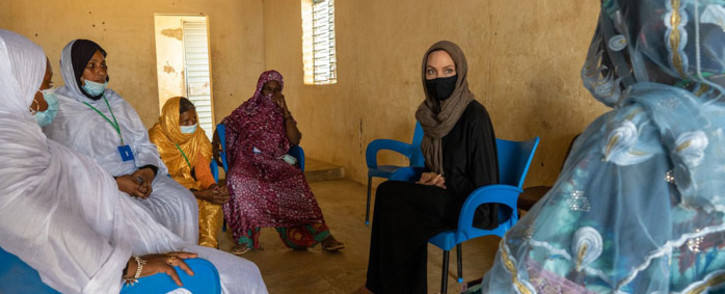 UNHCR ambassador, Angelina Jolie (in black), speaks to women at the refugee camp in Goudebou in Burkina Faso on 20 June 2021. Picture: @Refugees/Twitter