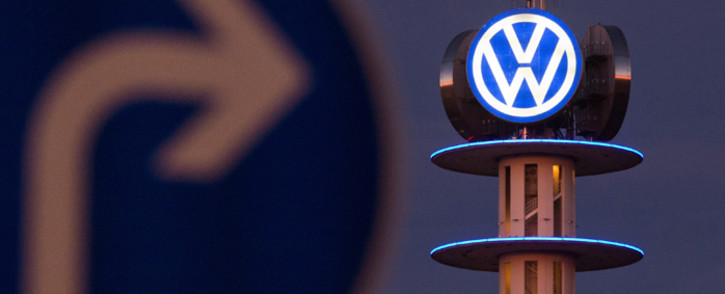 A street sign can be seen in front of the illuminated logo of German car maker Volkswagen (VW) on 10 December 2015 in Hanover, central Germany. Picture: AFP.
