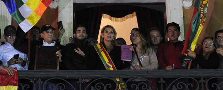 Deputy Senate speaker Jeanine Anez (C), accompanied by opposition leader in the eastern Santa Cruz region, Luis Fernando Camacho (2-L) among others, speaks from the balcony of the Quemado Palace in La Paz after proclaiming herself Bolivia's new interim president in a session of Congress that failed to reach a quorum, on 12 November 2019. Picture: AFP