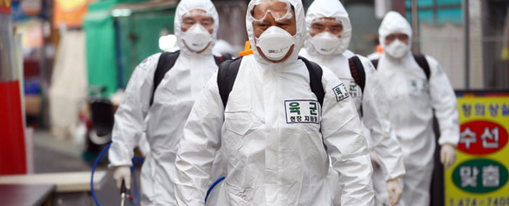 South Korean soldiers wearing protective gear spray disinfectant as part of preventive measures against the spread of the COVID-19 coronavirus, at a market in Daegu on 2 March 2020. Picture: AFP