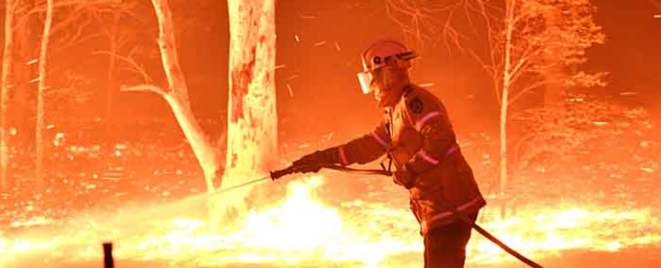 FILE: This picture taken on 31 December 2019 shows a firefighter hosing down trees and flying embers in an effort to secure nearby houses from bushfires near the town of Nowra in the Australian state of New South Wales. Picture: AFP