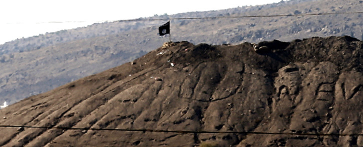 FILE: An Islamic State flag flies on a hill overlooking the Syrian town of Kobani, as seen from the border with Turkey in Suruc district, near Sanliurfa, Turkey, 7 October 2014. Picture: Sedat Suna/EPA.