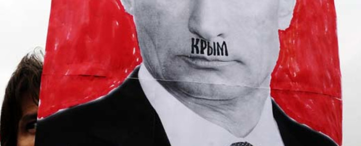 A woman holds up a portrait of Russian President Vladimir Putin with the word Crimea written above his lip, in reference to Hitler's mustache, as she demonstrates against Russian intervention in Ukraine during a rally in St. Petersburg on March 8, 2014. Picture: AFP.