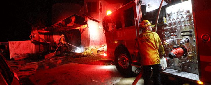 Los Angeles County Fire Department firefighters work at a home destroyed by the Tick Fire on October 24, 2019 in Canyon Country, California. Picture: AFP.