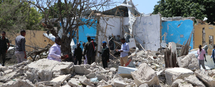 FILE: People stand in the rubble at a car suicide car bomb scene on 2 September 2018 in Mogadishu. Picture: AFP.