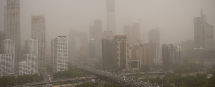 FILE: Parts of the central business district are shrouded in a dust storm in Beijing. Picture: AFP
