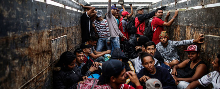 FILE: Venezuelan migrants travel aboard a truck after leaving the CEBAF (bi-national border care centre) facilities in Tumbes, Peru, near the border with Ecuador, on 1 November 2018.