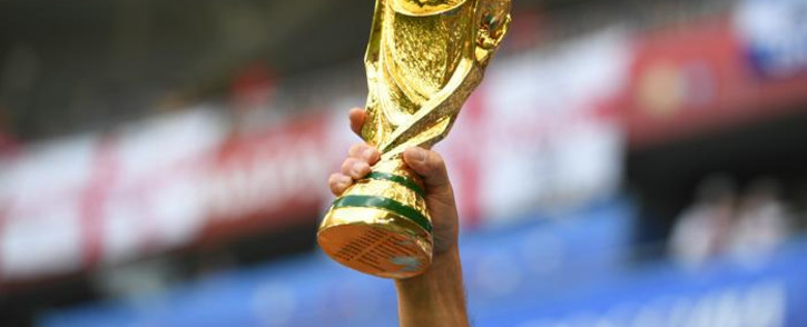 A fan raises a replica of the World Cup trophy. Picture: AFP.