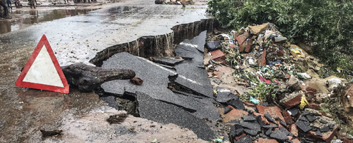 Residents stand next to a road partially destroyed by floods after heavy downpours in Pemba, on 28 April 2019, after the destruction caused by Cyclone Kenneth. Picture: AFP