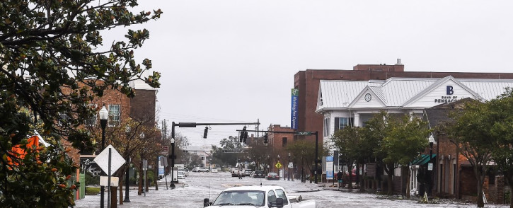 """A city worker drives through the flooded street during Hurricane Sally in downtown Pensacola, Florida on September 16, 2020. Hurricane Sally barrelled into the US Gulf Coast early Wednesday, with forecasts of drenching rains that could provoke """"historic"""" and potentially deadly flash floods."""