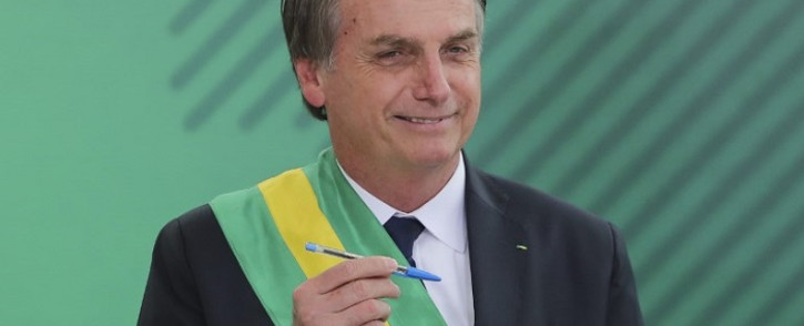 Brazil' President Jair Bolsonaro poses with the pen used during the swearing-in ceremony for the ministers at the Planalto Palace in Brasilia on 1 January 2019, after his own inauguration at the national Congress. Picture: AFP.