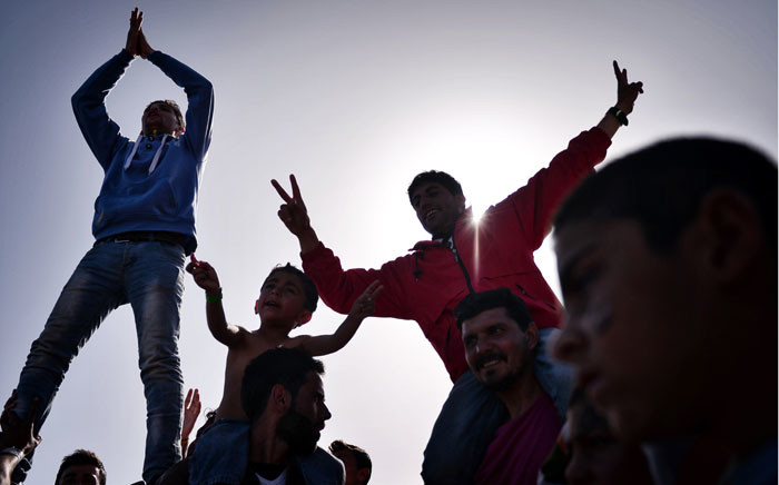 FILE: Kurdish refugees who managed to leave the VIAL detention center on the island of Chios are seen as they protest against deportations to Turkey at the island's port where they are camping out on 5 April 2016. Picture: Louisa Gouliamaki/AFP.