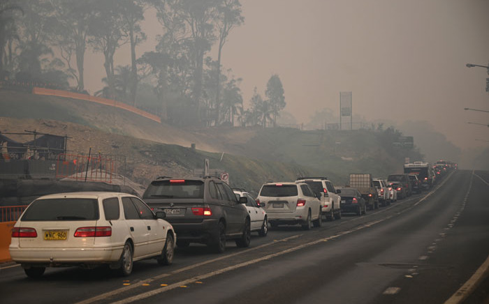 FILE: Cars line up to leave the town of Batemans Bay in New South Wales to head north on 2 January 2020. Picture: AFP