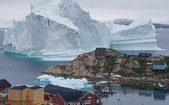 This picture was taken on 13 July 2018 shows an iceberg behind houses and buildings after it grounded outside the village of Innarsuit, an island settlement in the Avannaata municipality in northwestern Greenland. Picture: AFP.
