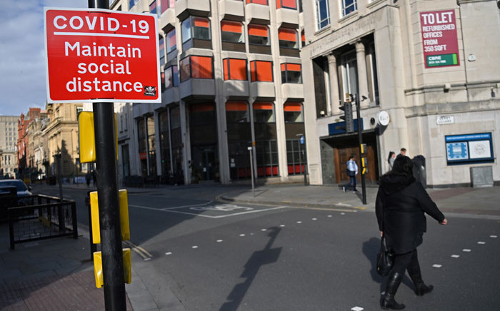 FILE: A pedestrian passes a social distancing sign as they cross an empty road in Liverpool, north-west England on 14 October 2020, as new local lockdown measures come in to force to help stem a second wave of the novel coronavirus. Picture: AFP