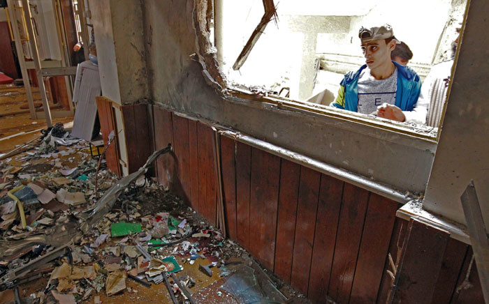 A Libyan youth inspects the interior of a mosque in Benghazi on 9 February 2018, after it was hit with a twin bomb attack. Picture: AFP