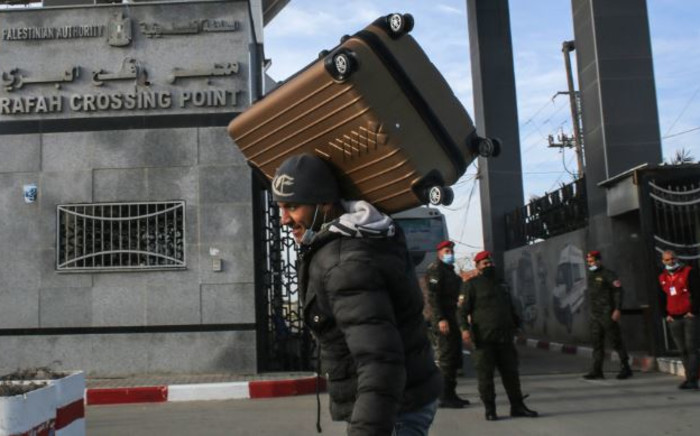 A man carries a suitcase on his shoulder while members of the Palestinian security forces loyal to Hamas, mask-clad due to the coronavirus pandemic, stand guard at the Rafah border crossing with Egypt, in the southern Gaza Strip, on 9 February 2021, which reopened after an Egyptian announcement to let through incoming traffic until further notice. Picture: SAID KHATIB/AFP
