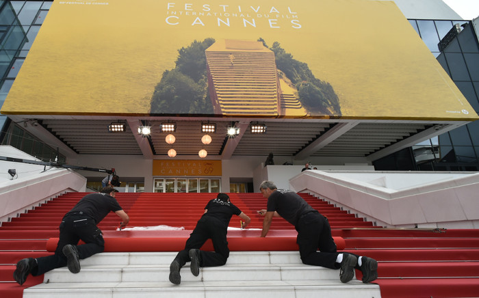 FILE: Staff members lay out the red carpet outside the Palais des Festivals in the southeastern French city of Cannes on 100 May, 2016 on the eve of the opening ceremony of the 69th Cannes Film Festival. Picture: AFP.