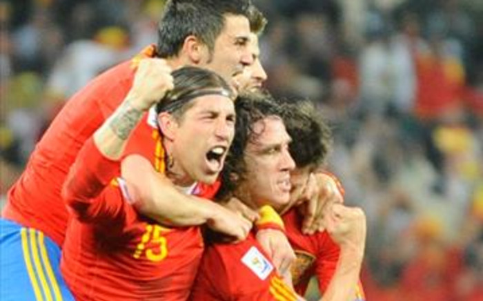 Teammates celebrate with Spain's defender Carles Puyol (R) after a goal that saw the team advance to the finals of the World Cup. Picture: AFP.