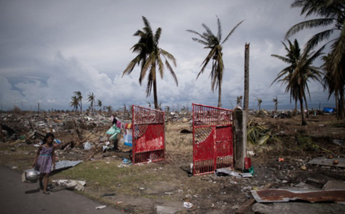 A typhoon victim walks past land ravaged by Typhoon Haiyan in Tacloban, on the eastern island of Leyte on 13 November, 2013. Picture:AFP