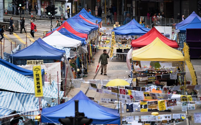 A man with a red umbrella walks past tents at the pro-democracy protest site in the Causeway Bay district of Hong Kong on 5 December, 2014. Picture: AFP.