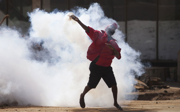 A supporter of Zimbabwe's MDC throws back a tear gas canister as protesters clash with police during a march against police brutality on August 24, 2016 in Harare, Zimbabwe. Picture: AFP