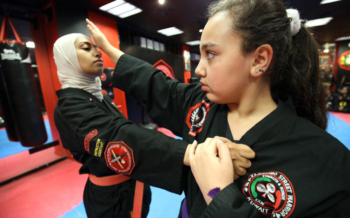 FILE: Kuwaiti Asma Hasnawi (L), a Kajukenbo hybrid martial art assistant-master, practises with her daughter Riham, in a club in Kuwait City on 22 October 2018. Picture: AFP