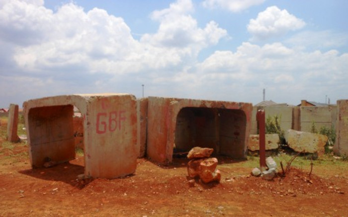 A small pile of rocks marks the spot where a Bekkersdal family has chosen to build a home on land belonging to the Rand Uranium mine. Abandoned construction materials are strewn around. Picture: Emily Corke/EWN.